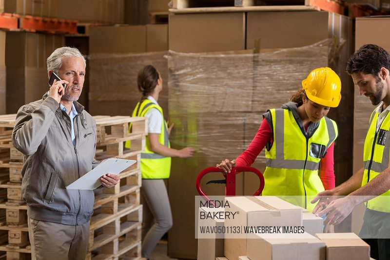 Warehouse manager and workers preparing a shipment in warehouse