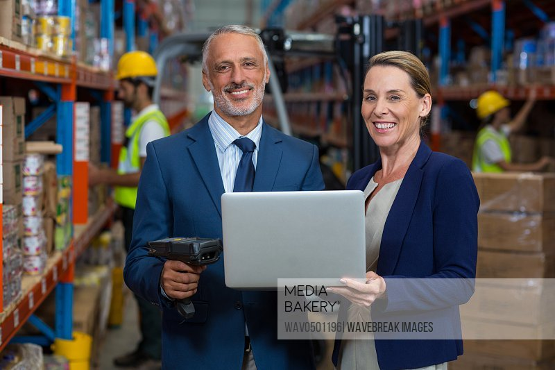 Warehouse manager and client using laptop in warehouse