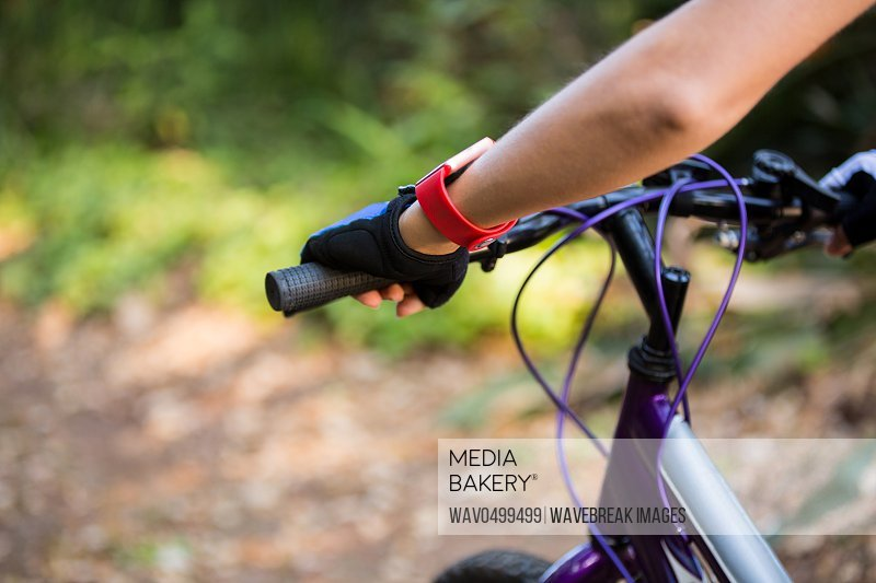 Mid section of female athletic standing with mountain bike in park