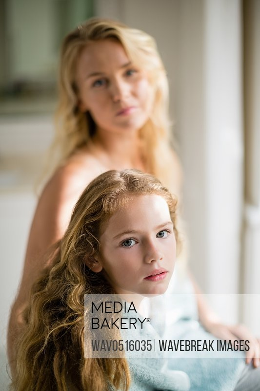 Mother and daughter in towel at bathroom