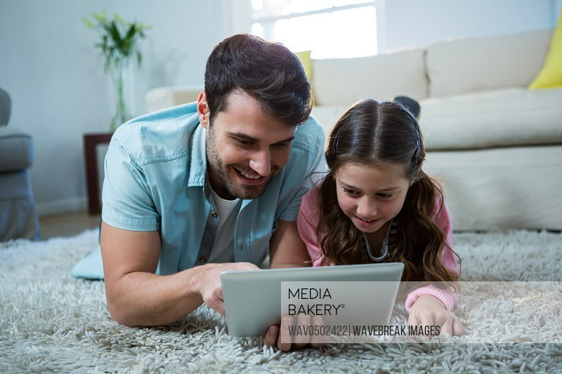 Father and daughter using digital tablet in the living room at home