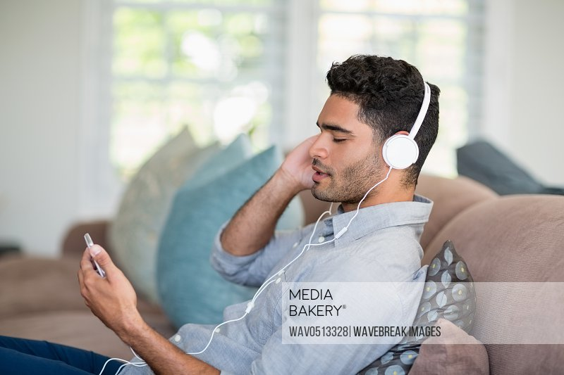 Man listening to music on mobile phone in living room