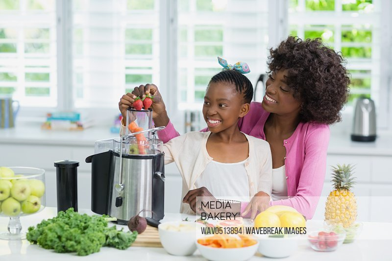 Smiling mother and daughter preparing strawberry smoothie in kitchen