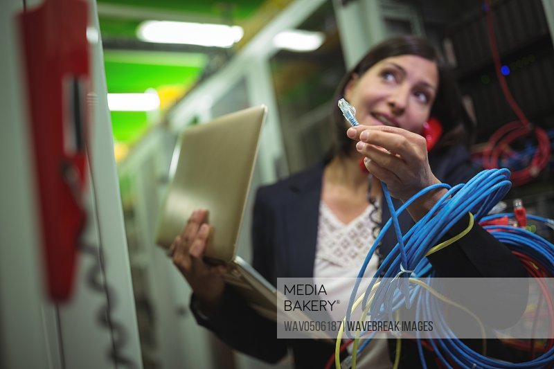 Technician holding internet cable while talking on phone in server room
