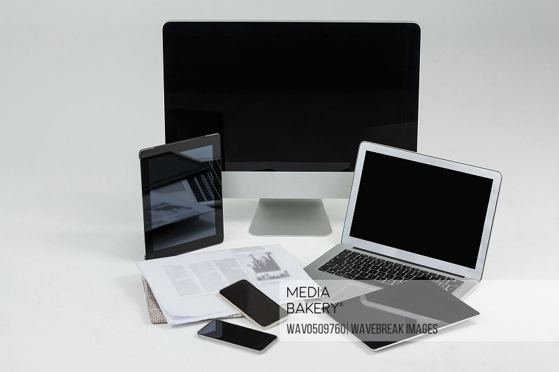Computer, laptop, digital tablets, mobile phones and newspaper on white background