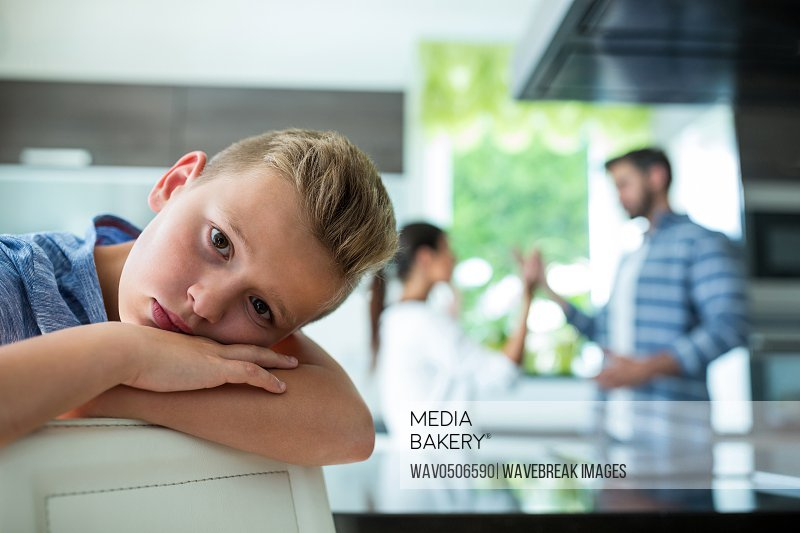 Sad boy leaning on chair while parents arguing in background at home