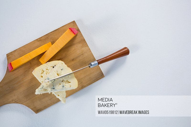 Variety of cheese with knife on wooden board