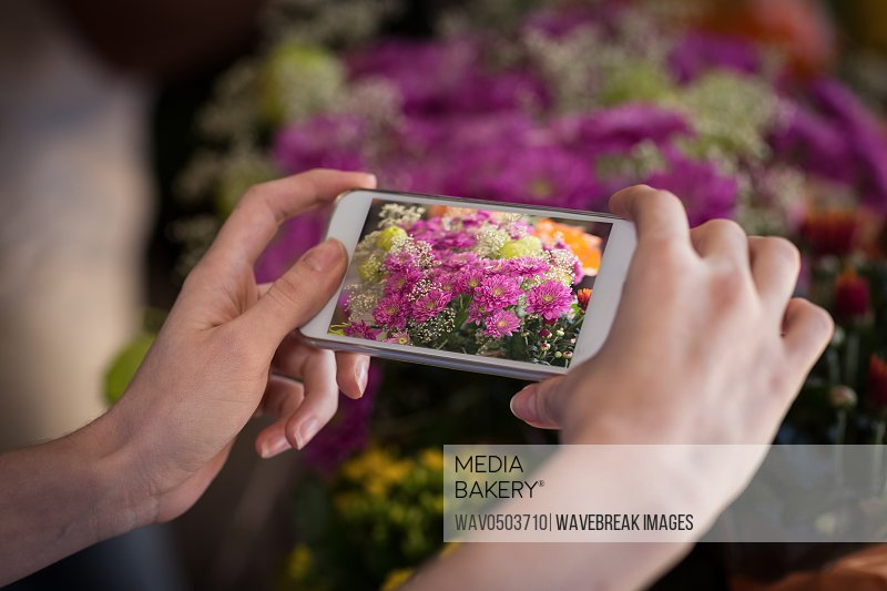 Woman's hand taking photograph of flower bouquet in flower shop