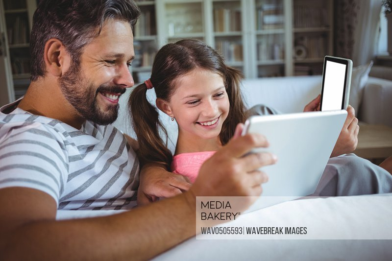 Happy father and daughter using digital tablet in living room at home