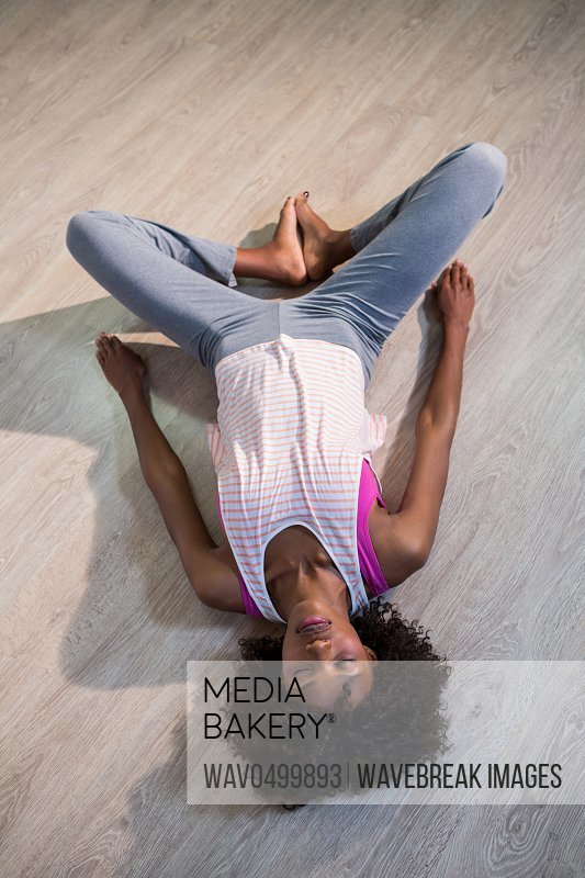 Woman in yoga corpse pose in gym