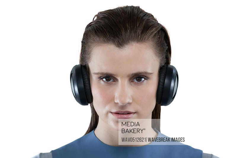 Portrait of beautiful woman listening to music on headphones against white background