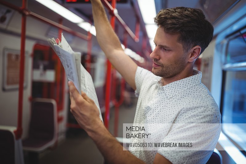Handsome man reading newspaper in train