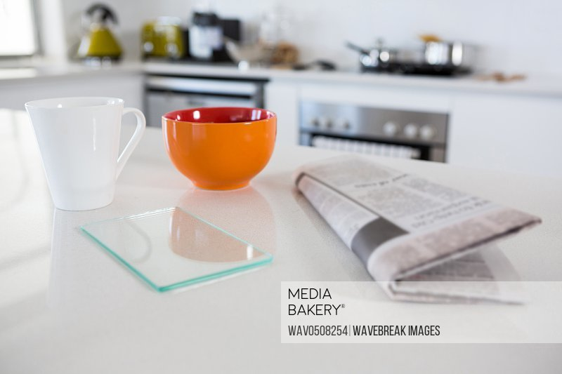 Breakfast bowl with coffee mug and newspaper in kitchen at home