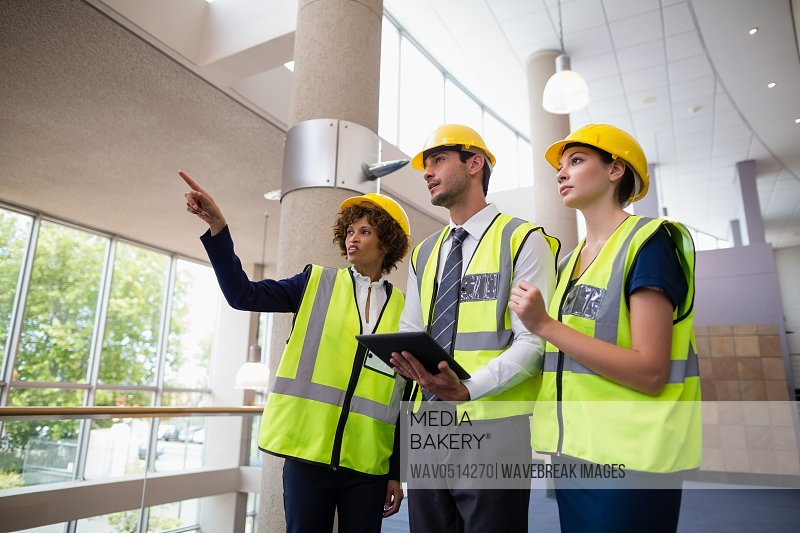 Architects discussing over digital tablet