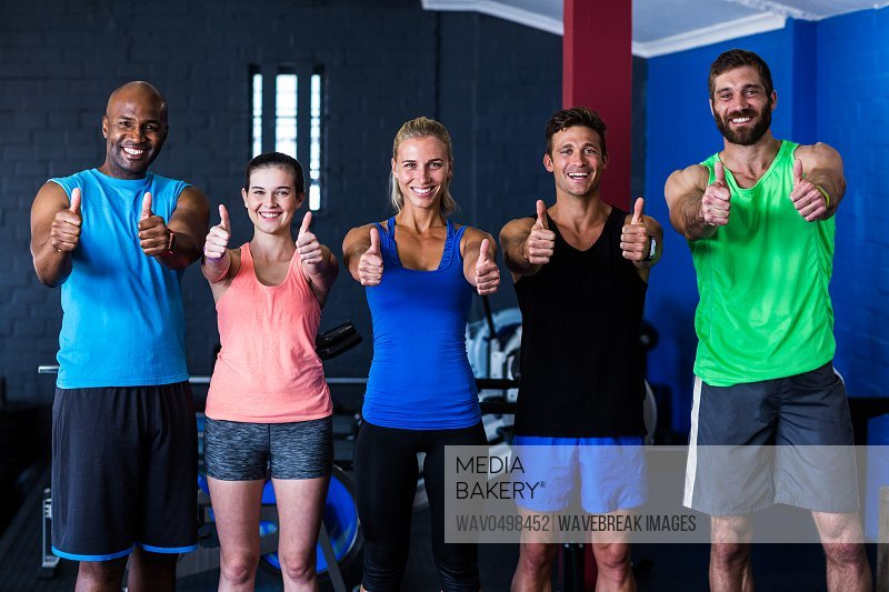 Portrait of smiling multi-ethnic friends showing thumbs up while standing in gym