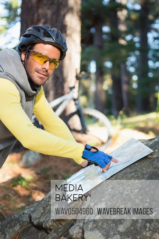 Portrait of mountain biker pointing at map in the forest
