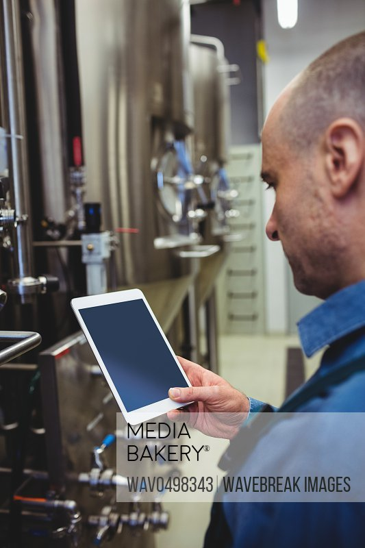 Side view of male owner using digital tablet by machinery at brewery