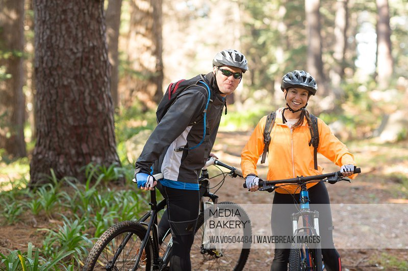 Portrait of biker couple standing with mountain bike on dirt track in countryside