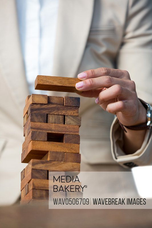 Business man placing wooden block on a towerA�in office