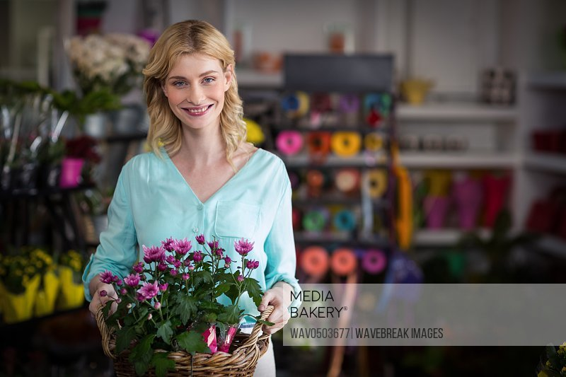 Portrait of happy female florist holding basket of flowers in the shop