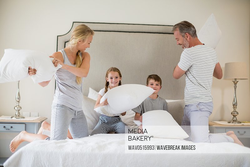 Cute family having a pillow fight in bedroom