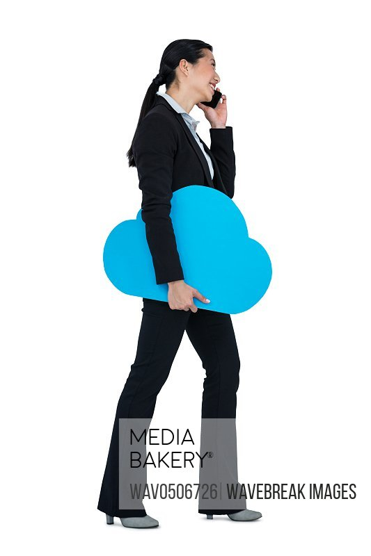 Smiling businesswoman holding cloud symbol and talking on mobile phone against white background