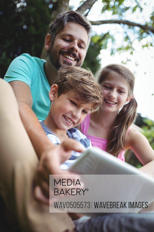 Happy father and kids using digital tablet in garden