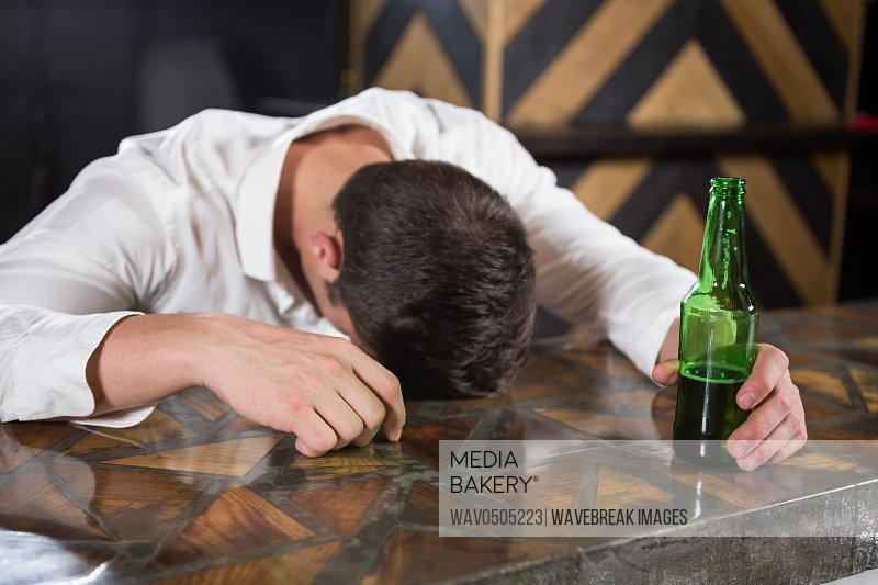 Drunk man lying on a counter with bottle of beer at bar