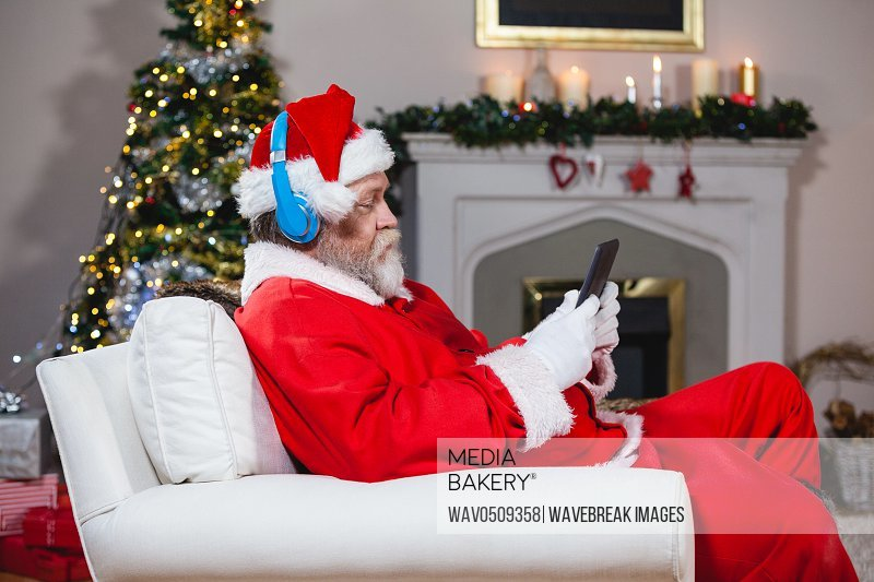 Santa claus using digital tablet at home