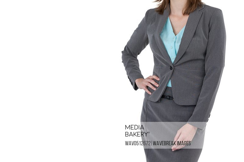 Mid section of businesswoman with hands on hip against white background