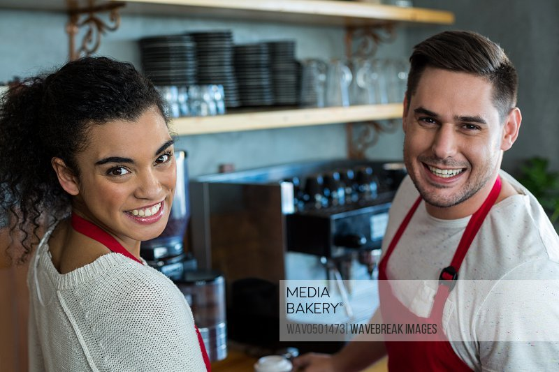 Portrait of smiling waitress and waiter in cafe