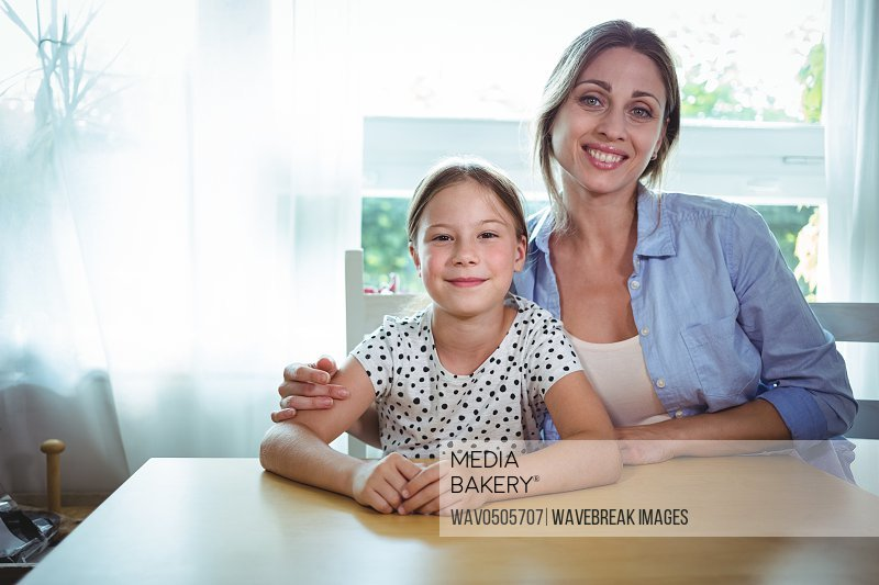 Portrait of happy mother and daughter leaning on the table at home