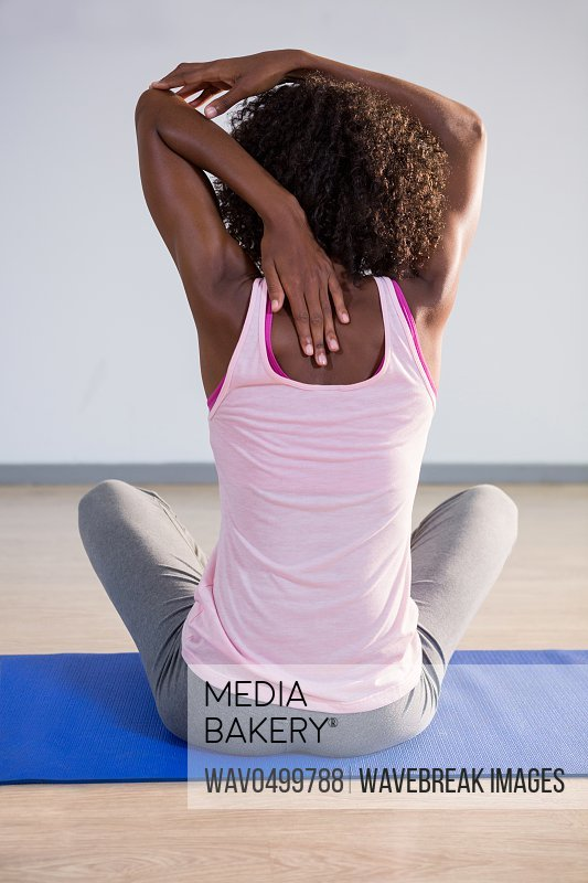 Rear view of woman performing stretching exercise on exercise mat