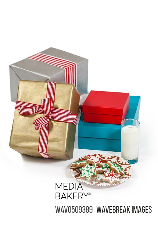 Close-up of milk and sweet food in plate with wrapped gift