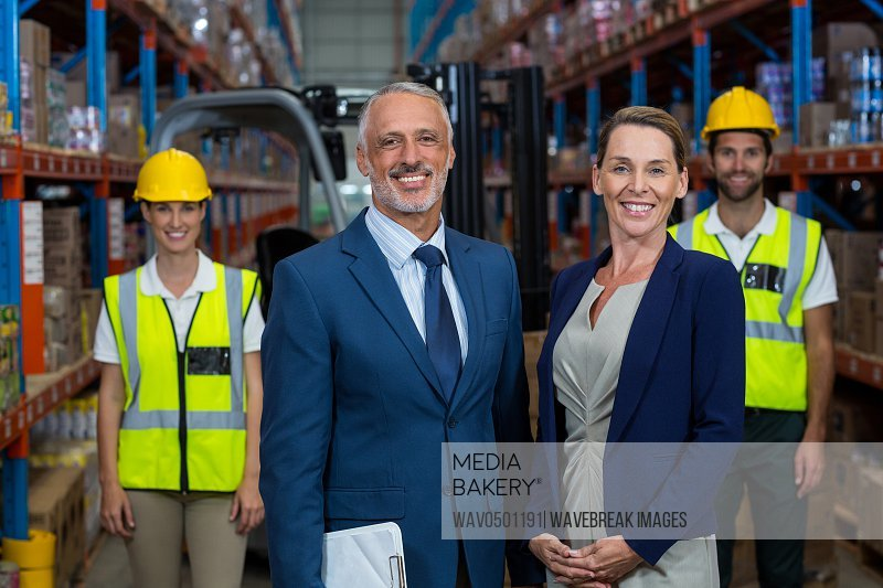 Portrait of warehouse manager standing with client in warehouse