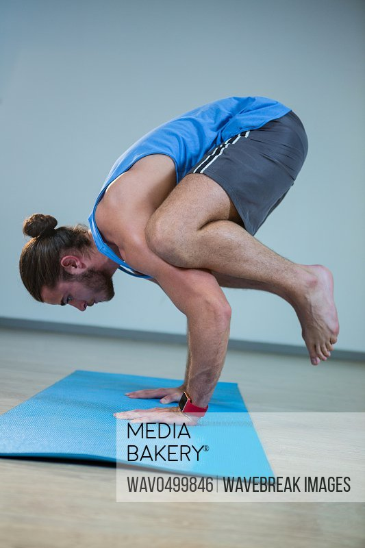 Man performing crow pose on exercise mat in gym