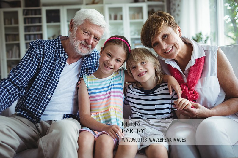 Portrait of grandparents sitting with their grandchildren at home