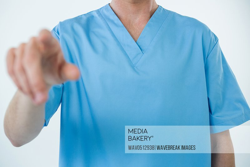 Mid section of male nurse touching an invisible screen against white background
