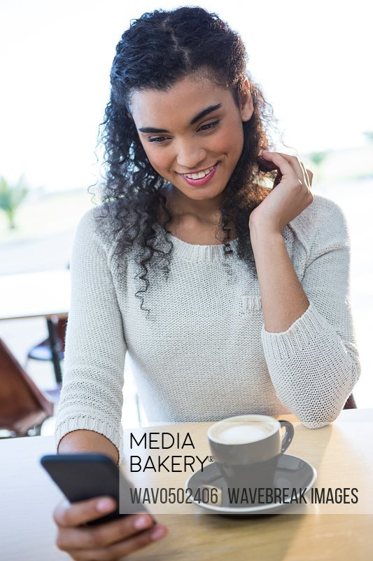 Smiling woman using mobile phone and a coffee cup on the table in coffee shop