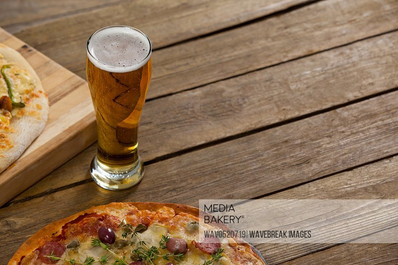 Delicious pizza served on wooden board with a glass of beer