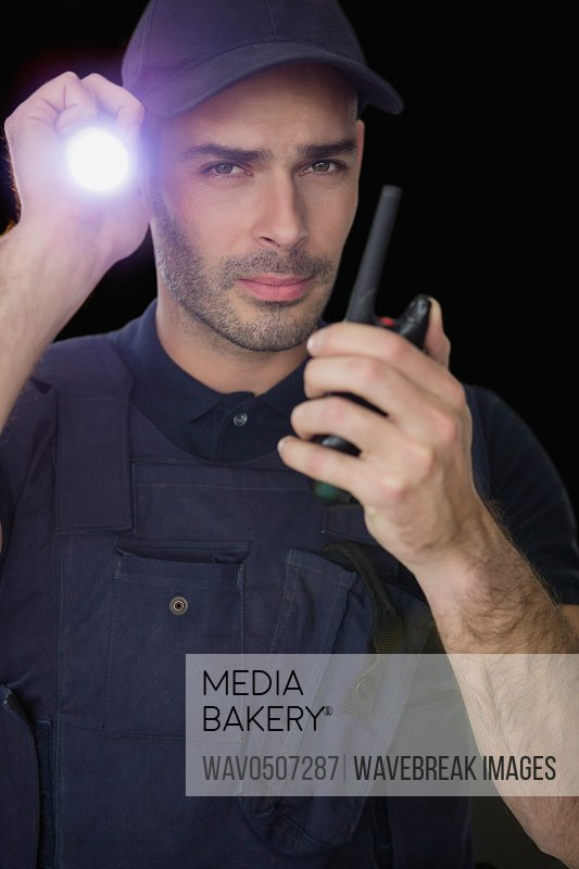 Security officer holding a torch and talking on walkie talkie against black background