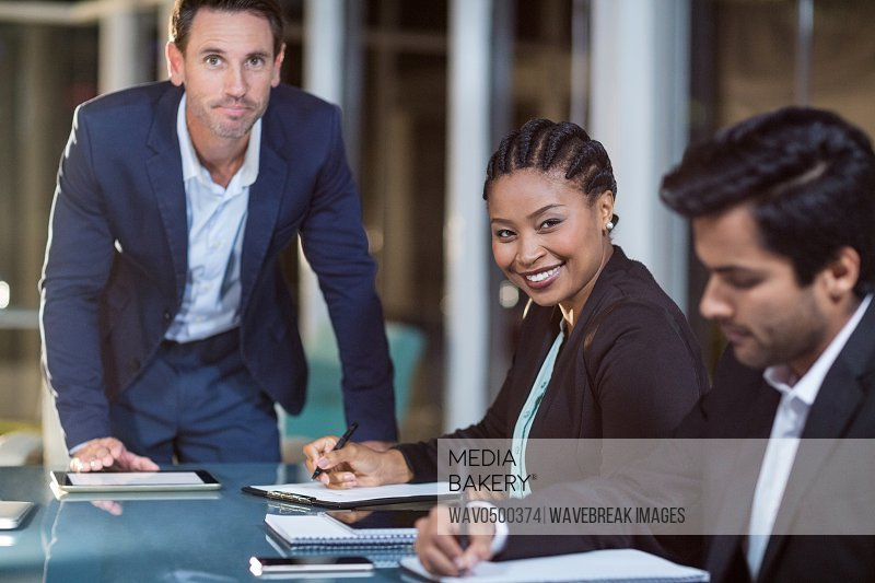 Portrait of businessman and businesswoman sitting in a meeting in the conference room