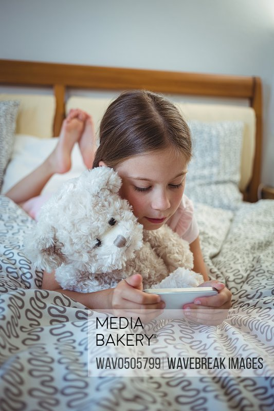 Happy girl lying on bed with a teddy bear and using mobile phone at home