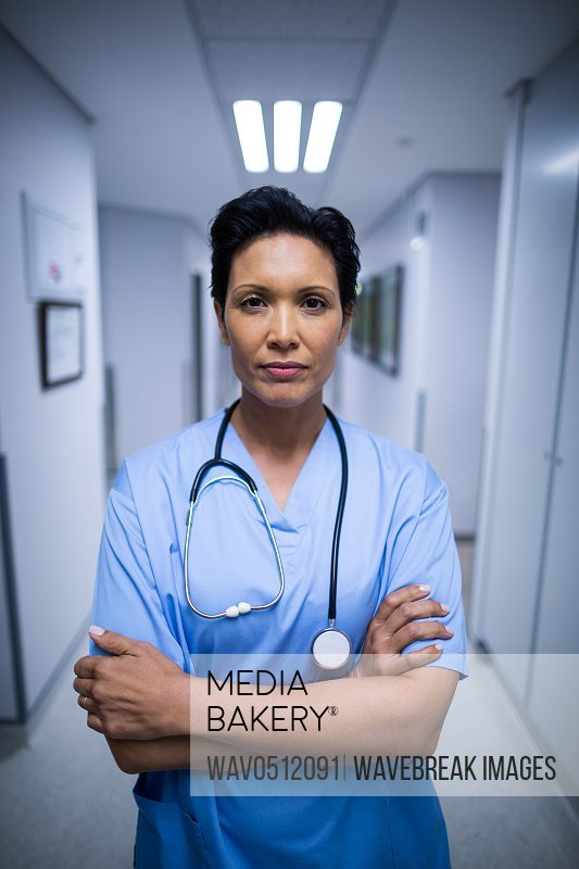 Portrait of female nurse standing with arms crossed in corridor of hospital