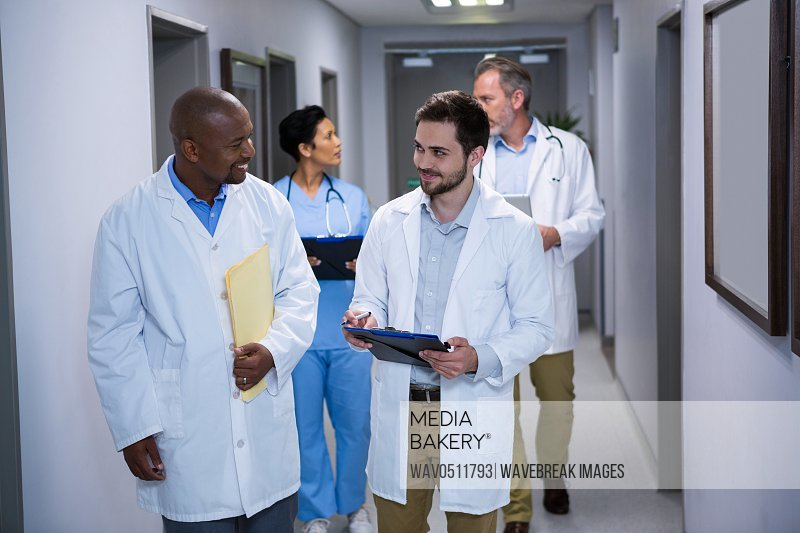 Doctors interacting with each other in corridor at hospital