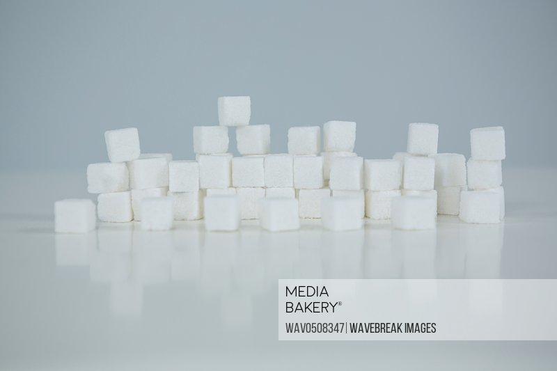 Close up of sugar cubes stacked on white background