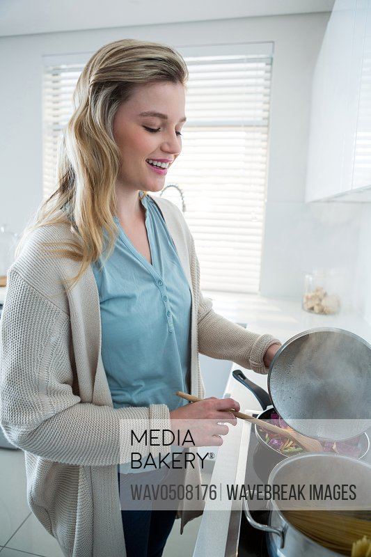Woman cooking food in kitchen at home