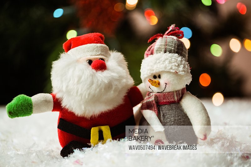 Santa claus and snowman on snow during christmas time