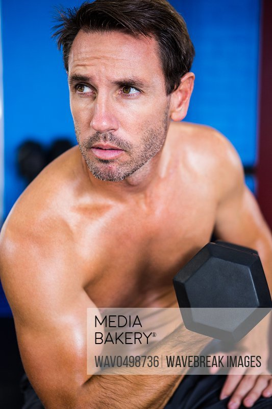 Shirtless athlete holding dumbbell in gym