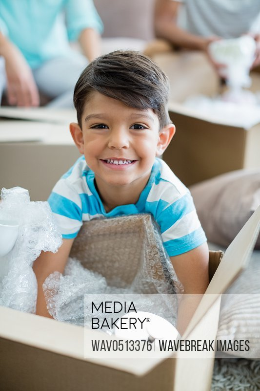 Boy unpacking carton boxes in living room at new home